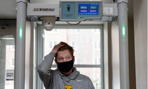 A college student walking through athermal sensor.